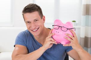 Happy Man Holding Piggybankの写真素材 [FYI00781086]