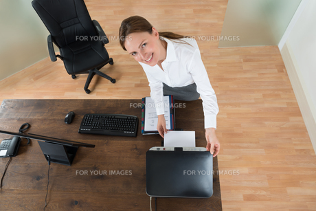 Young Businesswoman Using Printer In Officeの写真素材 [FYI00781123]