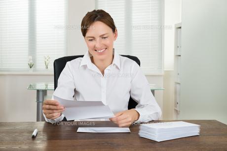 Businesswoman Holding Document At Deskの写真素材 [FYI00781132]