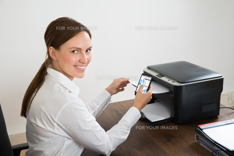 Businesswoman Using Mobile Phone For Printing Graphの写真素材 [FYI00781146]