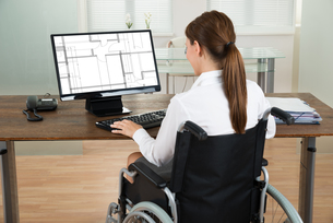 Architect On Wheelchair Looking At Blueprint On Computerの写真素材 [FYI00781162]