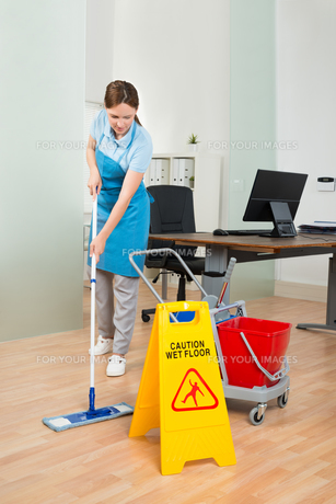 Female Janitor Cleaning Hardwood Floor In Officeの写真素材 [FYI00781181]