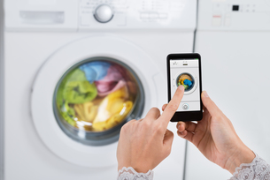 Person Hands Operating Washing Machine With Mobile Phoneの写真素材 [FYI00781191]