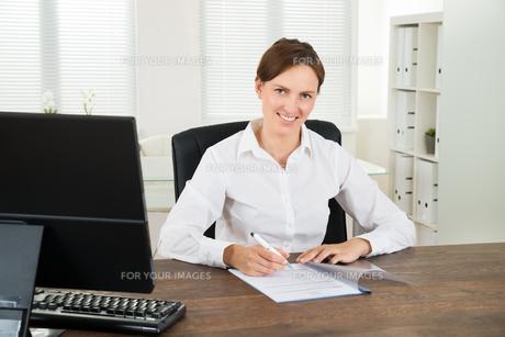 Businesswoman Writing On Documentの写真素材 [FYI00781204]