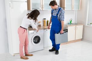 Woman Showing Damage In Washing Machine To Repairmanの写真素材 [FYI00781209]