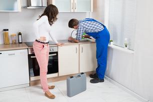 Woman Looking At Plumber Fixing Sinkの写真素材 [FYI00781223]