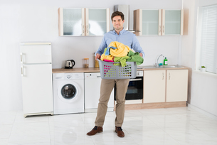 Man Carrying Basket With Heap Of Clothesの写真素材 [FYI00781226]