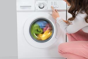 Woman Pressing Button Of Washing Machineの写真素材 [FYI00781235]