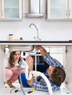 Worker Fixing Sink In Front Of Woman In Kitchenの写真素材 [FYI00781238]