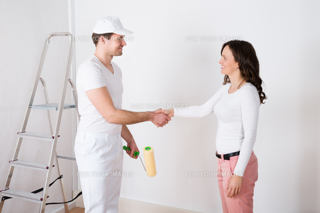 Woman Shaking Hands To Painter With Paint Roller At Homeの写真素材 [FYI00781243]