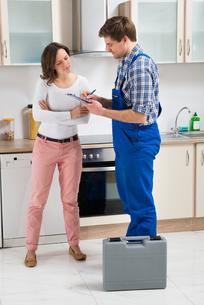 Woman And Repairman In Kitchenの写真素材 [FYI00781261]