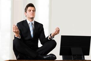 Businessman Sitting In Lotus Position At Deskの写真素材 [FYI00781271]