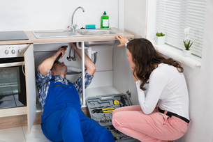 Repairman Repairing Pipe While Woman In The Kitchenの写真素材 [FYI00781272]