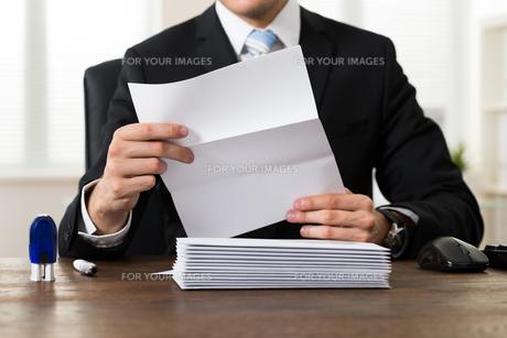 Businessman Holding Document At Deskの写真素材 [FYI00781273]
