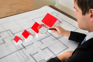 Architect Looking At House Models Through Magnifying Glassの写真素材 [FYI00781286]