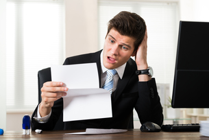 Shocked Businessman With Document In Officeの素材 [FYI00781287]