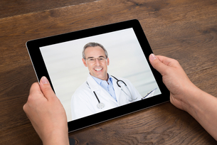 Person Videochatting With Doctor On Digital Tabletの写真素材 [FYI00781321]