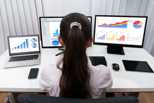 Businesswoman Analyzing Graphs On Computersの写真素材 [FYI00781356]