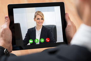 Businessperson Videochatting On Digital Tabletの写真素材 [FYI00781375]