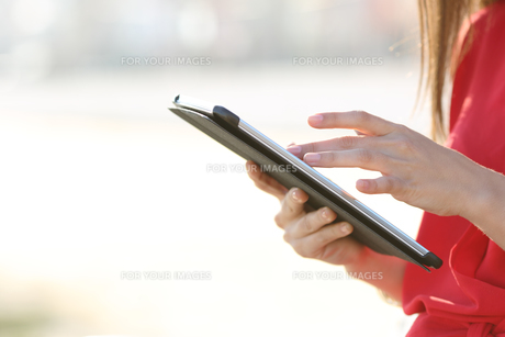 Woman hands browsing a tablet outdoorsの写真素材 [FYI00781612]