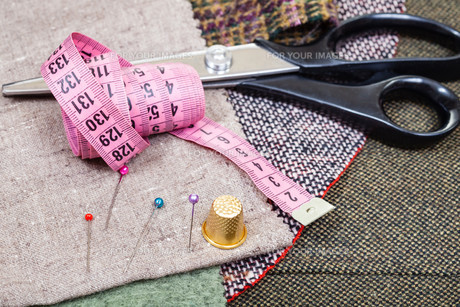 pink measure tape, pins, thimble, shears on clothの写真素材 [FYI00781749]