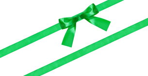 green bow knot on two diagonal silk bands isolatedの写真素材 [FYI00781820]