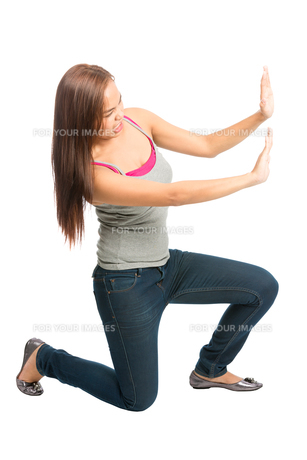 Woman Kneeling Arms Pushing Against Side Objectの写真素材 [FYI00782308]