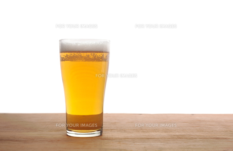 Glass of beer on wooden bar isolatedの素材 [FYI00782373]