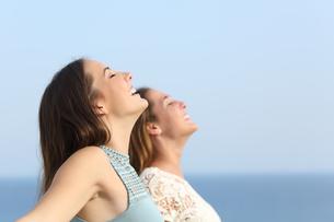 Two girls breathing deep fresh air on the beachの写真素材 [FYI00782483]
