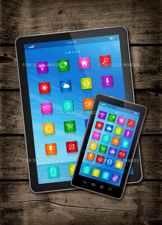 Smartphone and digital tablet PC with desktop icons on a dark wood tableの写真素材 [FYI00782589]