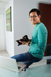 Asian Man Connect DSLR To PC Download Pictures On Laptopの写真素材 [FYI00782820]