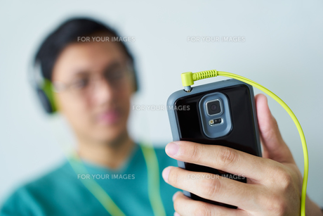 Chinese Man With Green Headphones Listens Music Podcast Phoneの写真素材 [FYI00782861]