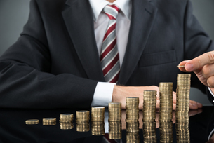 Businessman Placing Coin Over Stack Of Coinsの写真素材 [FYI00783086]