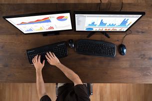 Man Analyzing Graphs On Computerの写真素材 [FYI00783087]