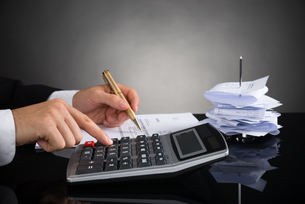 Businessperson Calculating Invoice At Deskの写真素材 [FYI00783102]