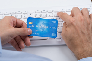 Hands Holding Credit Card On A Keyboardの写真素材 [FYI00783104]