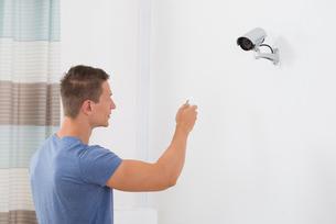 Man Operating Security Cameraの写真素材 [FYI00783122]