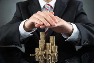 Businessman Saving Pile Of Coinsの写真素材 [FYI00783125]
