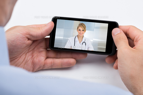Person Videochatting With Doctor On Mobile Phoneの写真素材 [FYI00783130]