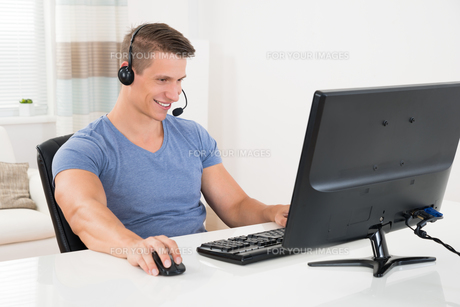 Man Using Desktop Computer And Headsetの写真素材 [FYI00783134]