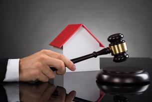 Judge With House Model Hitting Gavelの写真素材 [FYI00783135]