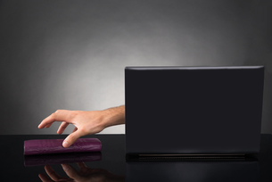 Person Hand Reaching Out From A Laptop Grabbing Walletの写真素材 [FYI00783142]