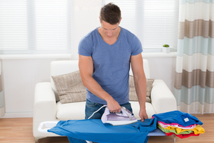 Young Man Ironing Clothesの写真素材 [FYI00783157]