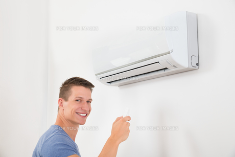 Man With Remote Control To Operate Air Conditionerの写真素材 [FYI00783166]