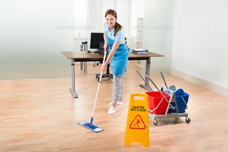Female Janitor Cleaning Hardwood Floor In Officeの写真素材 [FYI00783183]
