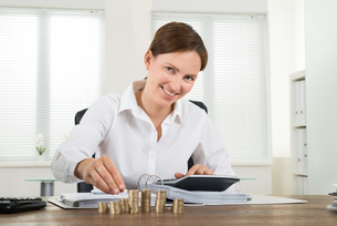 Businesswoman Calculating Invoice With Coins At Deskの写真素材 [FYI00783195]