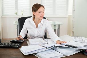 Businesswoman Calculating Financial Data At Deskの写真素材 [FYI00783201]