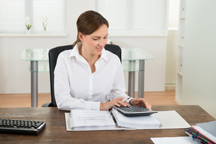 Businesswoman Calculating Invoiceの写真素材 [FYI00783220]