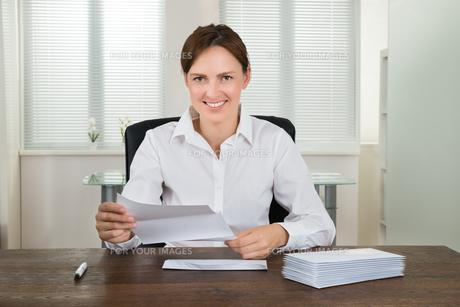 Businesswoman Holding Document At Deskの写真素材 [FYI00783222]