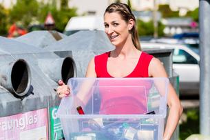 Frau auf Entsorgungshof wirft Flaschen in Containerの素材 [FYI00783232]
